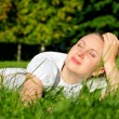 Young woman relaxing on the grass in park — Stock Photo