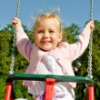 Smiling little girl on swing in the park — Stock Photo
