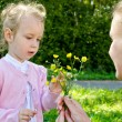 Mother and daughter gathering flowers in the park — Stock Photo