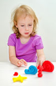 Liitle girl learning to use plasticine — Stock Photo