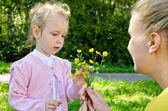 Madre e hija recogiendo flores en el parque — Foto de Stock
