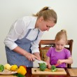 Mother and daughter preparing food. Cutting broccoli with knife. — Stock Photo