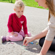 Mother and daughter drawing with chalk on asphalt — Stock Photo