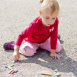 Little girl drawing with chalk on asphalt — Stock Photo