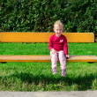 Little girl sitting on the bench in the park — Stock Photo