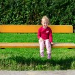 Stock Photo: Little girl sitting on the bench in the park