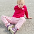Cute little girl sitting on asphalt — Stock Photo