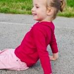 Cute little girl sitting on asphalt — Stock Photo #12439011