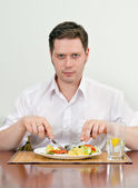 Handsome man eating with fork and knife — Stock fotografie