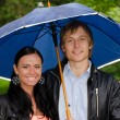Portrait of young couple under umbrella in the park — Stock Photo