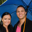 Portrait of young couple under umbrella in the park — Stock Photo #12704613