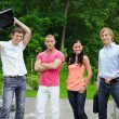 Group of cheerful students in the park — Stock Photo
