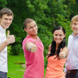 Happy friends raising hands with thumb up in the park — Stock Photo #12704644