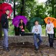 Group of friends under colourful umbrellas — Stock Photo