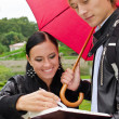 Two students under umbrella in the park — Stock Photo