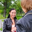 Female student chatting with friend outdoors — Stock Photo