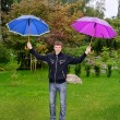 Young man with two umbrellas outdoors — Stock Photo #12704782