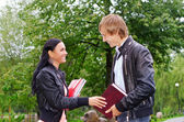 Female student talking with friend outdoors — Stock Photo