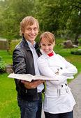 Dva studenti s otevřenou knihu v parku — Stock fotografie