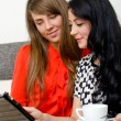 Two young woman with tablet pc sitting on the sofa — Stock Photo #13121338
