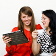 Two young woman using tablet pc — Stock Photo