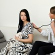 Female doctor examines patient at home — Stock Photo #13121485