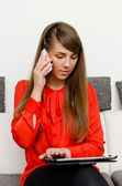Pretty girl with tablet computer talking on the phone — Stockfoto