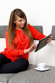 Pretty girl with tablet computer sitting on the sofa — Stok fotoğraf