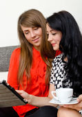 Two young woman with tablet pc sitting on the sofa — Stok fotoğraf