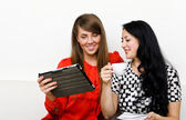 Two young woman using tablet pc — Stockfoto