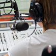 Stock Photo: Rear view of male dj working in front of microphone on radio