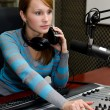 Portrait of female dj working in front of a microphone on the radio — Stock Photo