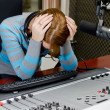 Portrait of depressed female dj working in front of a microphone on the rad — Stock Photo