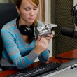Portrait of female dj stting in front of a microphone on the radio with ala — Stock Photo