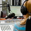 Stock Photo: Rear view of female dj working in front of microphone on radio