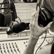 Stock Photo: Rear view of female dj working in front of microphone on radio. Blach