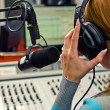 Rear view of female dj working in front of a microphone on the radio — Stock Photo #13592810