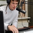 Stock Photo: Portrait of male dj working in front of microphone on radio