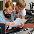 Colleagues examine broadcast list in studio - Stock Photo
