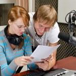 Colleagues examine broadcast list in studio — Stock Photo #13592828