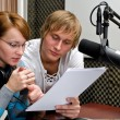 Colleagues examine broadcast list in studio — Stock Photo #13592836