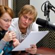 Stock Photo: Colleagues examine broadcast list in studio