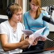 Colleagues examine broadcast list in studio — Stock Photo