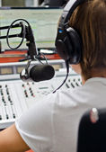 Rear view of male dj working in front of a microphone on the radio — Stock Photo