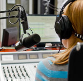 Rear view of female dj working in front of a microphone on the radio — Foto de Stock
