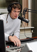 Portrait of male dj working in front of a microphone on the radio — Stock Photo