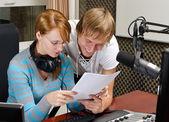 Colleagues examine broadcast list in studio — Stock Photo