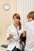 Young female doctor measuring patient — Stock Photo