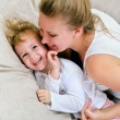 Young woman and little girl having fun in bed — Stock Photo