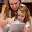 Young woman and little girl using tablet pc sitting on bed - Stock Photo